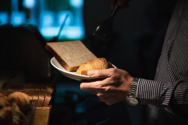 De bedrijfsmens eet het amerikaanse ontbijt dat in een hotel wordt geplaatst