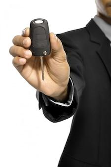 De bedrijfsmens geeft autosleutel die over witte achtergrond wordt geïsoleerd