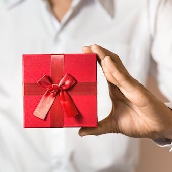 De bedrijfsmens houdt rode giftdoos in handen.