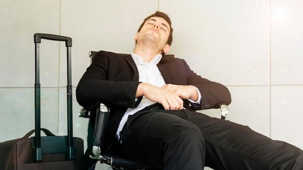 De bedrijfsmens is vermoeid en voelt slaperig en zit op stoel tijdens het wachten op zaken die bij de luchthaven reizen.