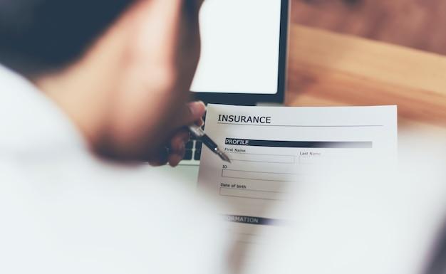De bedrijfsmens op het kantoor vult verzekeringsbeleid in. om toekomstige incidenten te voorkomen.