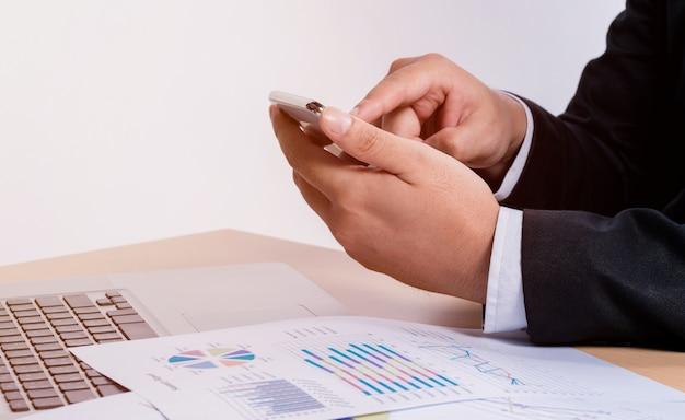 De bedrijfsmens raakt de mobiele telefoon op het team van de vergaderingslijst om op het kantoor te werken