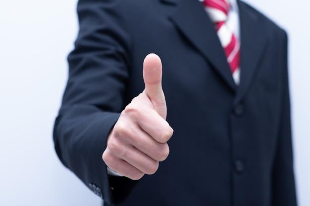 De bedrijfsmens toont duimen op close-upsymbole positief of goed werk.