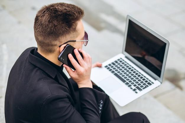 De bedrijfsmens zit op treden buiten bureau, werkend aan laptop computer, uitnodigend telefoon. stijlvol mannelijk model in zwarte jas. jonge man met een mobiele telefoon zittend op de trappen