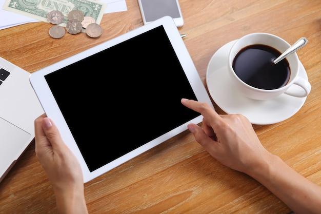 De bedrijfsmensen gebruiken tabletmodel met bureaukantoorbehoeften en zwarte koffie op houten bureau