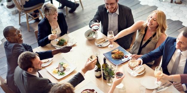 De bedrijfsmensen juichen het genieten van voedsel van concept toe