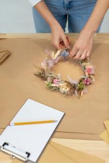De bedrijfspersoon die van de close-up een kroon van bloemen hoge mening creëert