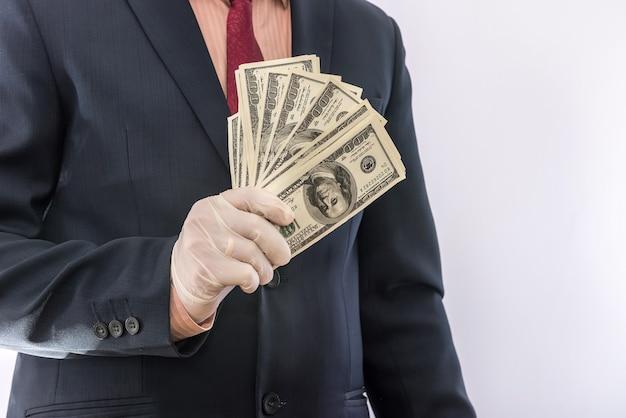 De bedrijfspersoon dient blauwe beschermende handschoenen met geld in dat op witte achtergrond wordt geïsoleerd. bewaar beschermingsconcept covid 19 coronavirus