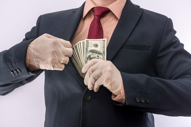 De bedrijfspersoon dient blauwe beschermende handschoenen met geld in dat op witte achtergrond wordt geïsoleerd