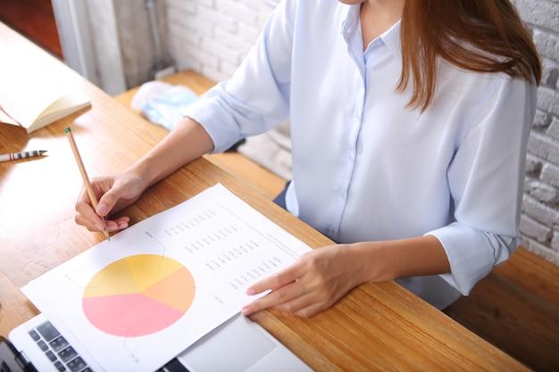 De bedrijfsvrouw analyseert bedrijfsrapportdocument op houten bureau