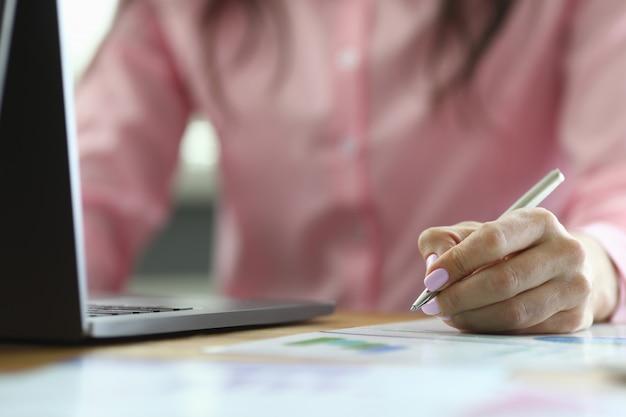 De bedrijfsvrouw controleert gegevens in rapport en op laptop
