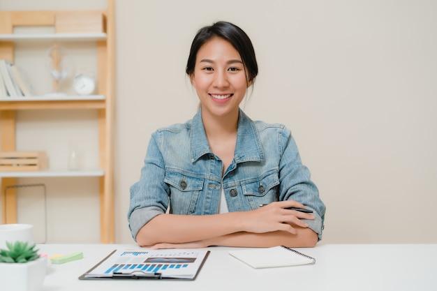 De bedrijfsvrouw die van azië het gelukkige glimlachen voelen en aan camera kijken terwijl ontspan thuis bureau.