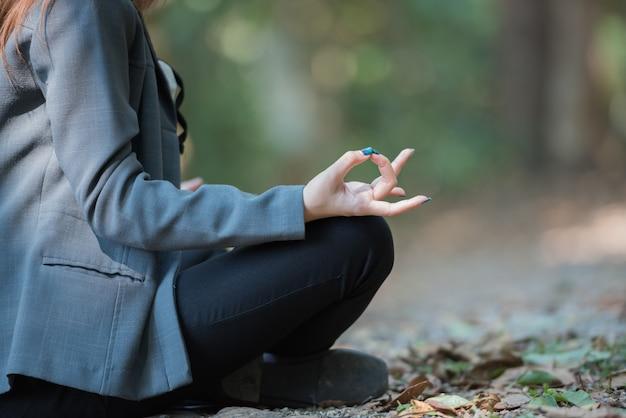 De bedrijfsvrouw die yogameditatie in het natuurreservaat doen, sluit omhoog.