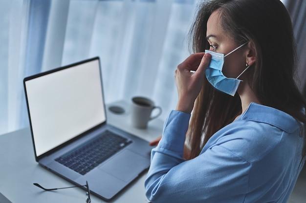 De bedrijfsvrouw draagt online een medisch beschermend masker werkend van huis bij laptop tijdens zelfisolatie en quarantaine.