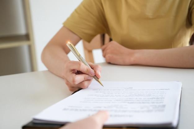 De bedrijfsvrouw en de partner ondertekenen een professionele documentovereenkomst van de contractinvestering in vergaderzaal.