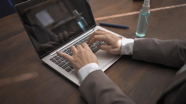 De bedrijfsvrouw gebruikt computer terwijl het zitten bij houten bureaulijst met een ontsmettingsmiddelnevel op het