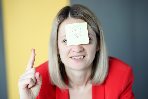 De bedrijfsvrouw heeft sticker met geschilderde gloeilamp op haar gezicht. nieuwe ideeën voor bedrijfsconcept