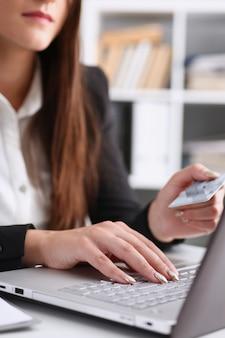 De bedrijfsvrouw in het bureau houdt een plastic debetkaart van het krediet in haar hand