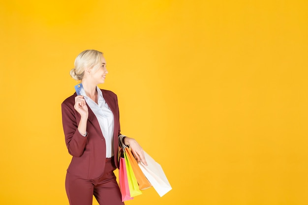 De bedrijfsvrouw is gelukkig met het winkelen op studio gele achtergrond