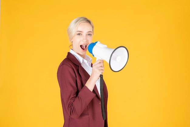 De bedrijfsvrouw kondigt van megafoon op gele achtergrond aan