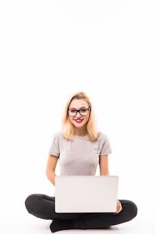 De bedrijfsvrouw met laptop in zwarte jeans zit op de vloer