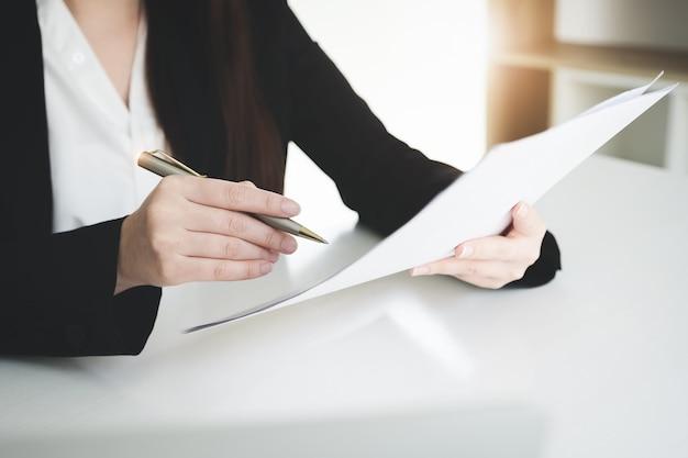 De bedrijfsvrouw ondertekent een professionele het documentovereenkomst van de contractinvestering in vergaderzaal.