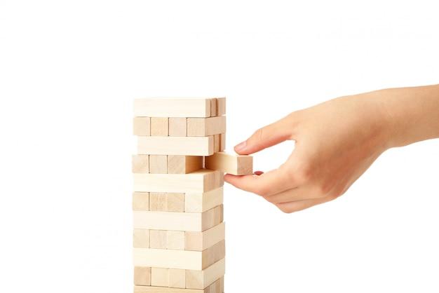 De bedrijfsvrouw plukt met de hand en zette laatste stukblok van het houten raadsel. houten blok dat op witte muur wordt geïsoleerd