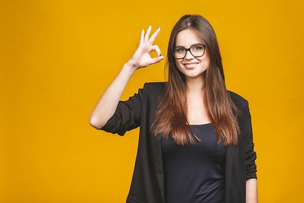 De bedrijfsvrouw toont ok symbool. toothy het glimlachen bedrijfsvrouwenportret dat tegen gele muur wordt geïsoleerd.