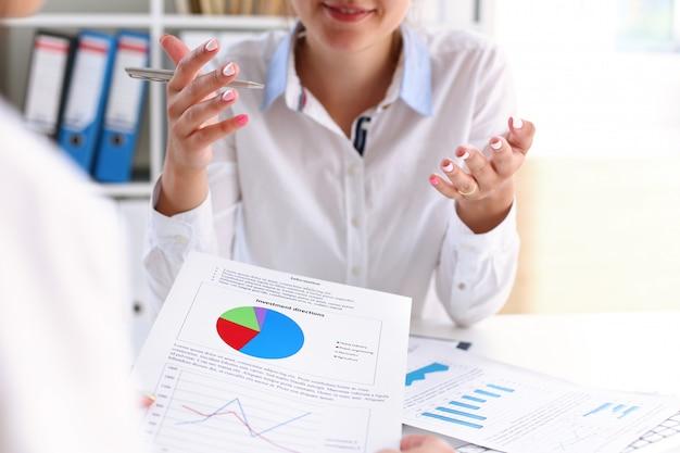 De bedrijfsvrouw verklaart financiële statistieken van de werknemer