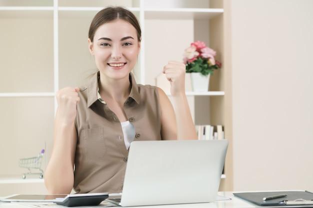 De bedrijfsvrouw werkt aan laptop computer die succesvol gevoel uitdrukken.