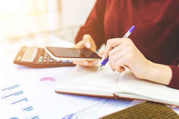 De bedrijfsvrouw werkt thuis, maakt het verre werk thuis, met laptop en met notitieboekje, nota's over de telefoon