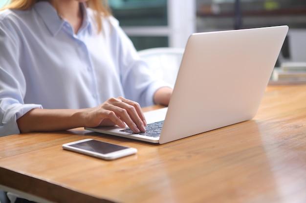 De bedrijfsvrouw zit op stoel met het gebruiken van laptop op houten bureau