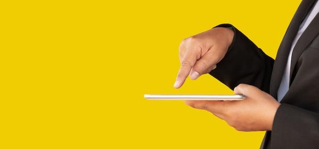 De bedrijfsvrouwen gebruiken tabletten om aan een gele achtergrond te werken