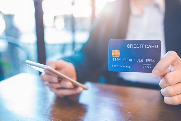 De bedrijfsvrouwenhand houdt een blauwe creditcard en gebruikt een celtelefoon in het bureau.