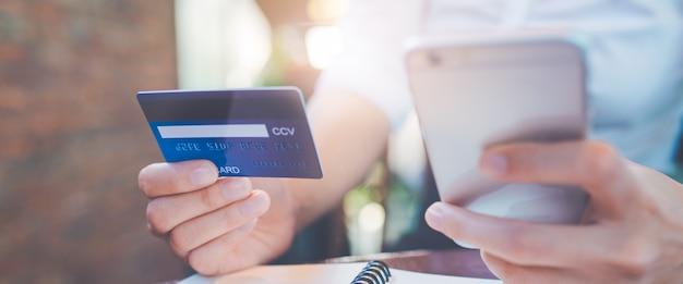 De bedrijfsvrouwenhand houdt een blauwe creditcard en gebruikt mobiele telefoons.