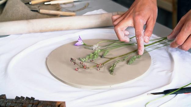De beeldhouwer maakt een originele tekening op een blanco klei.