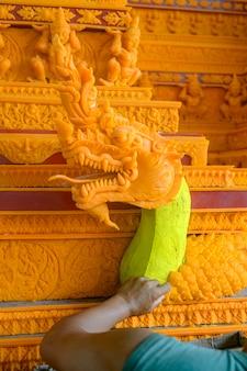 De beeldhouwer plakte was met was. om waskasteel te maken doe mee met het waskasteelparadefestival in sakon nakhon, thailand