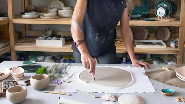 De beeldhouwer werkt in zijn atelier en maakt keramische producten.