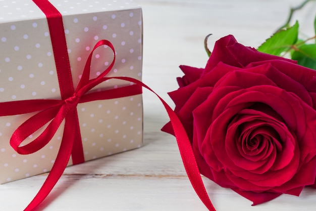 De beige doos van de stipgift met rode lintboog en bautiful rode rozen op houten achtergrond. wenskaart voor vakantie.