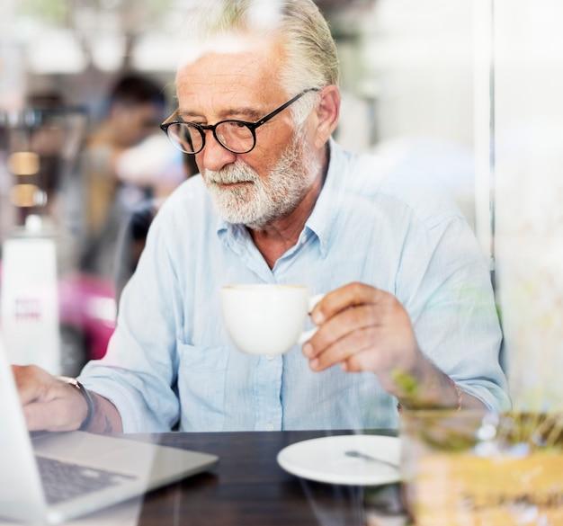 De bejaarde gebruikt computerlaptop