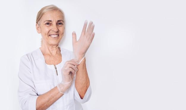 De bejaarde glimlachende gelukkige rijpe vrouwenarts of de verpleegster in een witte medische laag zetten handschoenen aan die persoonlijk geïsoleerd beschermingsmiddel dragen. gezondheidszorg en geneeskunde concept. covid-19 pandemische crisis