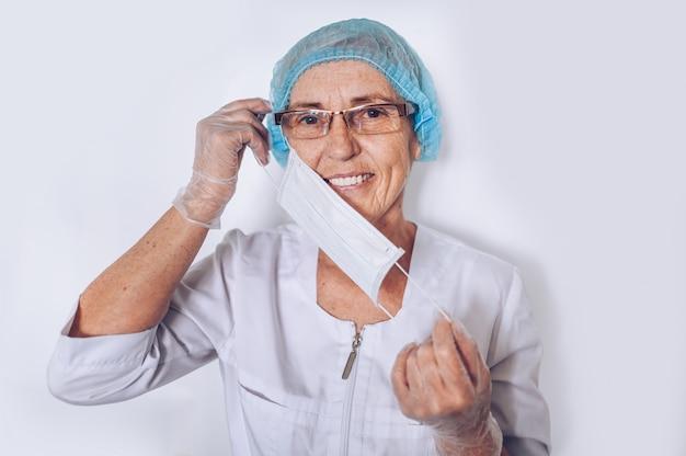 De bejaarde glimlachende rijpe vrouwenarts of de verpleegster in een witte medische laag, handschoenen, zetten gezichtsmasker op het dragen van geïsoleerd persoonlijk beschermingsmiddel. gezondheidszorg en geneeskunde concept. covid19 pandemische crisis