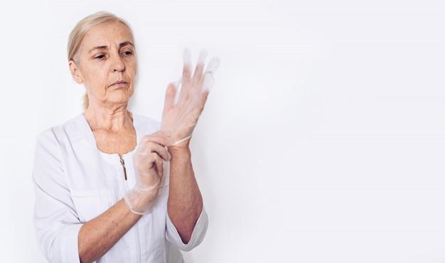De bejaarde hogere rijpe vrouwenarts of de verpleegster in een witte medische laag zetten handschoenen aan die persoonlijk geïsoleerd beschermingsmiddel dragen. gezondheidszorg en geneeskunde concept. covid-19 pandemische crisis