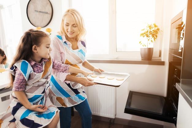 De bejaarde leert meisje om eigengemaakte koekjes te koken.