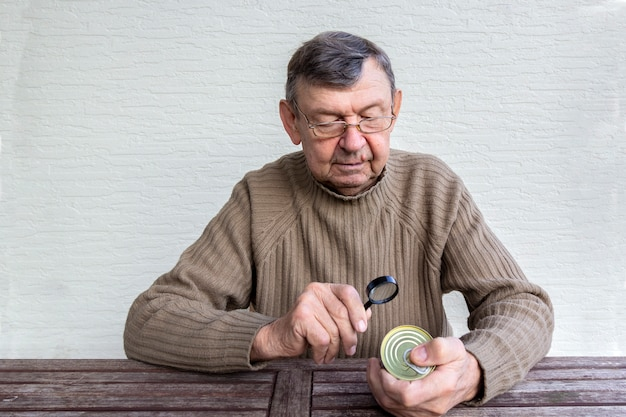 De bejaarde leest van voedselproduct met meer magnifier