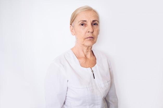 De bejaarde rijpe vermoeide uitgeputte vrouwenarts of de verpleegster in een witte medische laag die persoonlijk beschermingsmiddel dragen dat op wit wordt geïsoleerd. gezondheidszorg en geneeskunde concept. covid-19 pandemische crisis