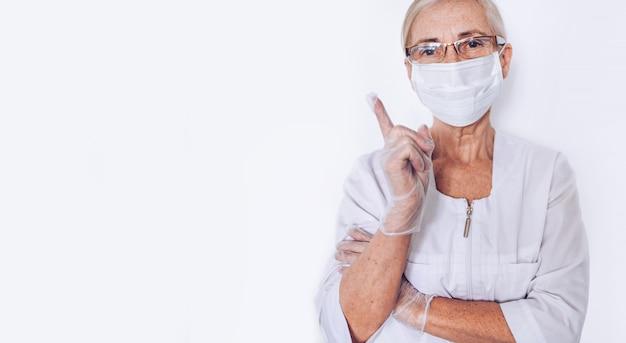 De bejaarde rijpe vrouwenarts of de verpleegster hieven vinger in een witte medische laag, handschoenen, gezichtsmasker op dat persoonlijk geïsoleerd beschermingsmateriaal draagt. gezondheidszorg en geneeskunde concept. covid-19 pandemische crisis