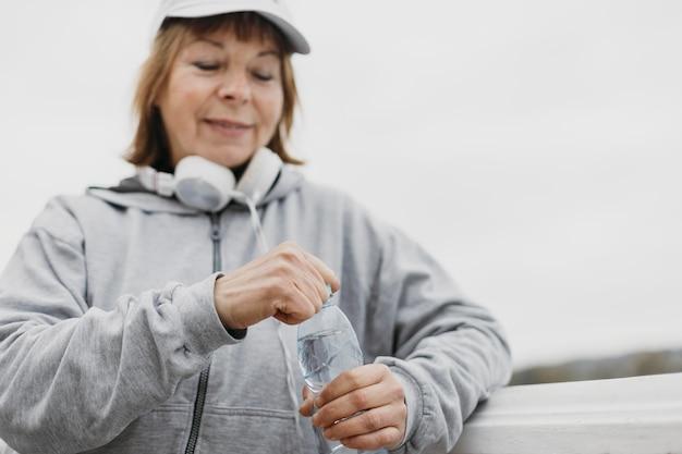De bejaarde vrouw van smiley met waterfles en hoofdtelefoons in openlucht
