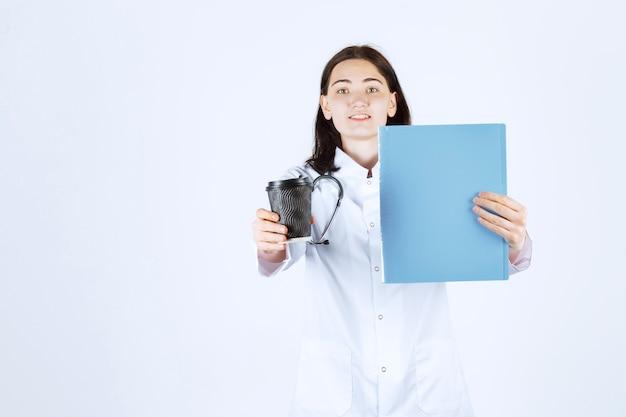 De bekende dokter toont haar dossier in haar linkerhand en haar koffie in haar rechterhand