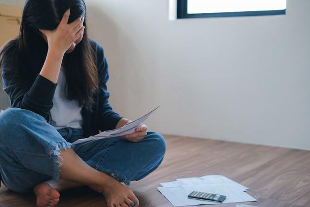 De beklemtoonde jonge aziatische vrouw ontmoet financieel probleem en creditcardschuld zonder terug te betalen geld.